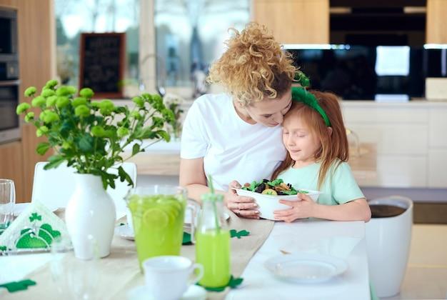 Retrato de mãe e filha abraçadas à mesa