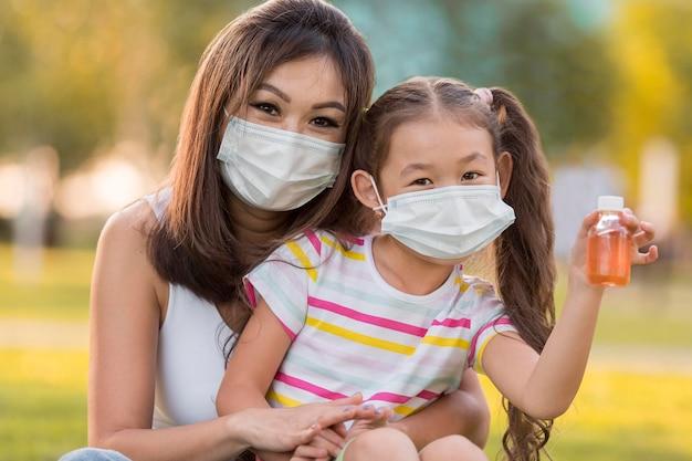 Retrato de mãe e filha asiática com máscaras
