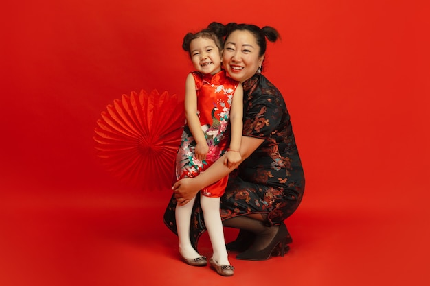 Retrato de mãe e filha asiático isolado em uma parede vermelha em roupas tradicionais