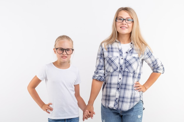 Retrato de mãe e filha com óculos na parede branca