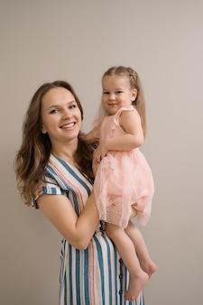 Retrato de mãe e filha em fundo bege
