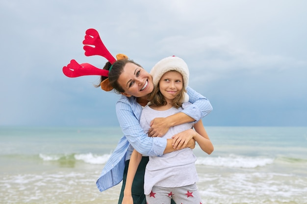 Retrato de mãe e filha felizes abraçando na praia com orelhas de rena