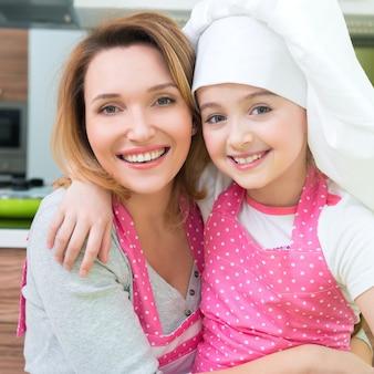 Retrato de mãe e filha felizes e sorridentes com avental rosa na cozinha