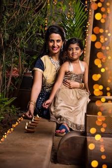 Retrato de mãe e filha indiana com clay diya e iluminação durante a celebração do festival de diwali