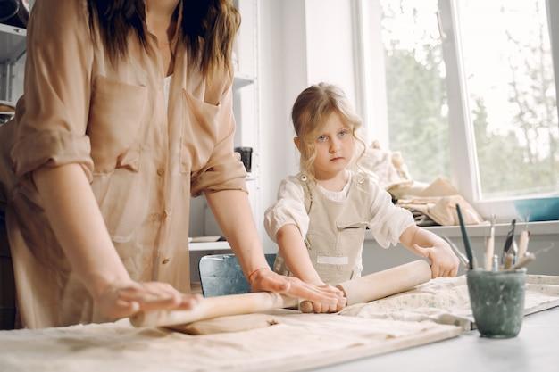 Retrato de mãe e filha juntos a moldar a argila