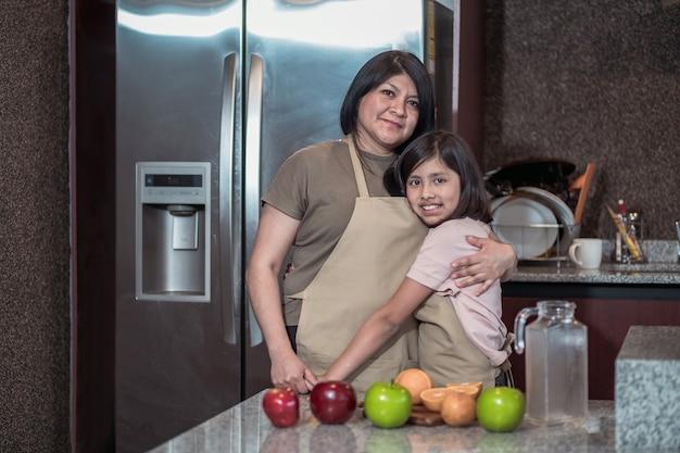 Retrato de mãe e filha mexicana na cozinha, dia das mães