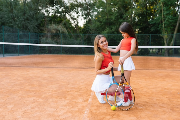 Retrato de mãe e filha na quadra de tênis