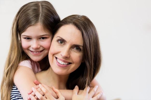 Retrato de mãe e filha que abraçam-se