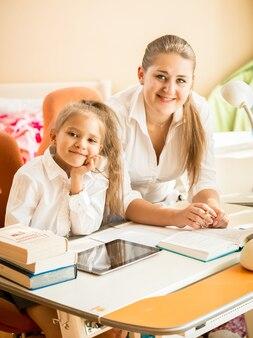 Retrato de mãe e filha sorrindo, sentadas na mesa e olhando para a câmera
