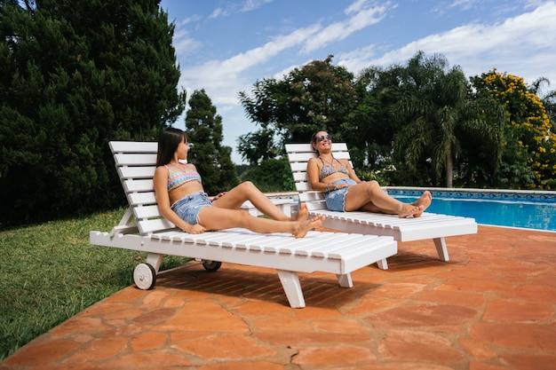 Retrato de mãe e filha tomando banho de sol na beira da piscina.
