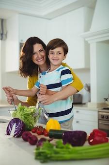 Retrato de mãe e filho misturando a salada na cozinha