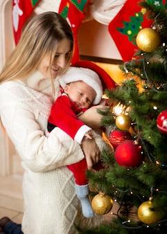 Retrato de mãe e filho recém-nascido decorando uma árvore de natal com enfeites