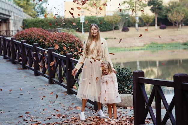 Retrato de mãe elegante e filha ao ar livre