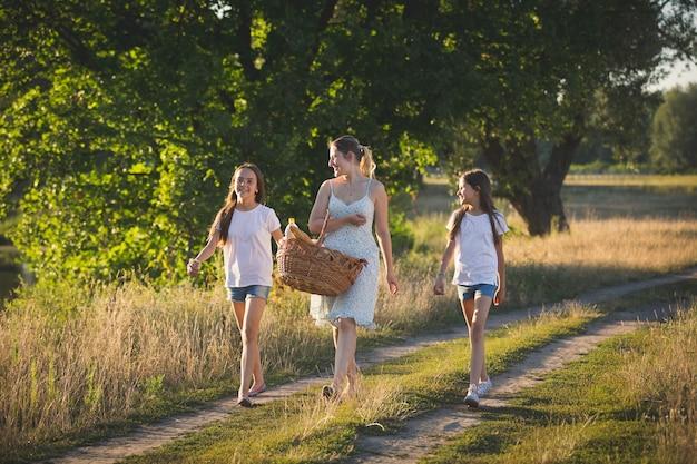 Retrato de mãe feliz com duas filhas caminhando à beira do rio em um prado