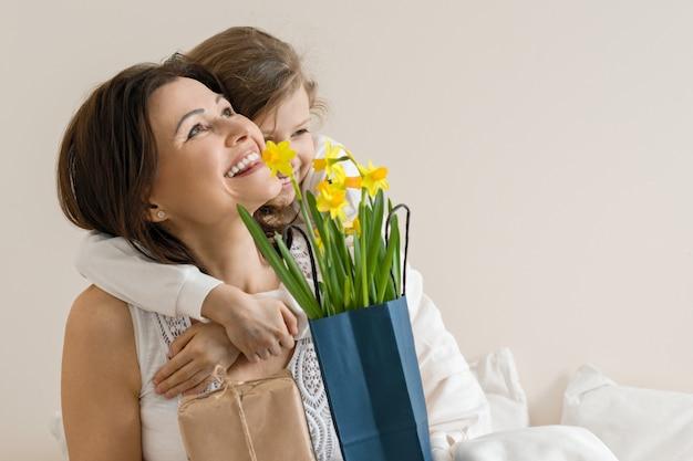 Retrato de mãe feliz e filha sorrindo e abraçando