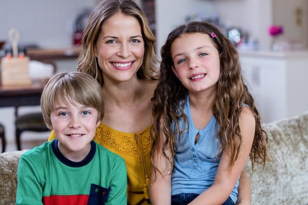 Retrato de mãe feliz e filhos sentados em um sofá