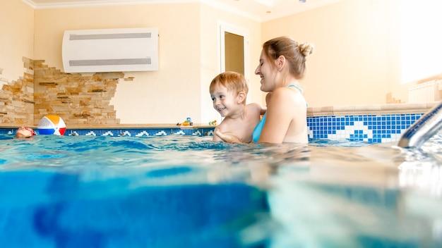 Retrato de mãe feliz e sorridente com filho de 3 anos de idade, nadando na piscina no ginásio. família relaxando, se divertindo e brincando na água