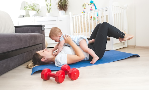 Retrato de mãe feliz fazendo exercícios em casa e se divertindo com o filho