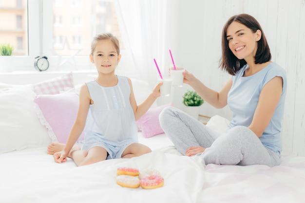 Retrato de mãe jovem feliz e sua filha pequena segurar copos de milk-shake
