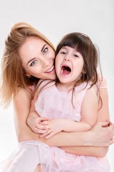 Retrato de mãe loira e doce filha em vestidos cor de rosa princesas abraçando e rindo em fundo cinza. família
