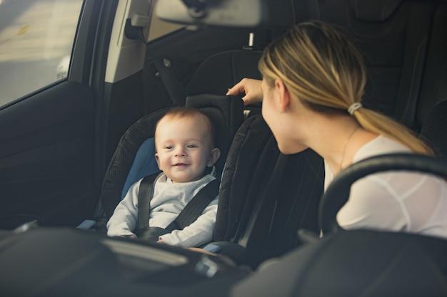 Retrato de mãe olhando para um bebê sentado no banco da frente do carro