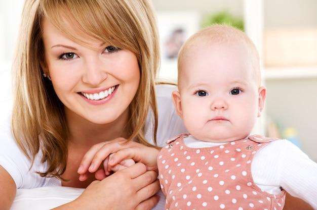 Retrato de mãe sorridente com bebê recém-nascido em casa