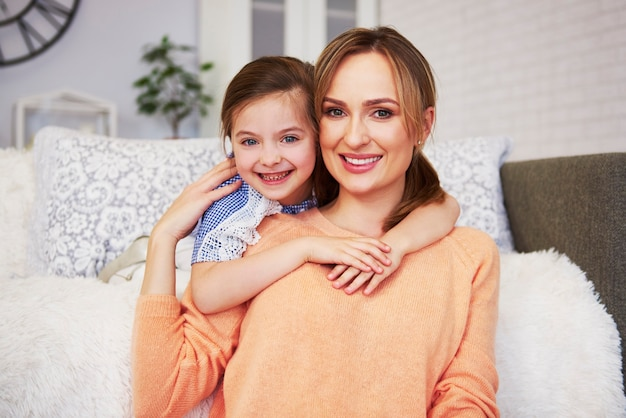 Retrato de mãe sorridente e filha olhando para a câmera