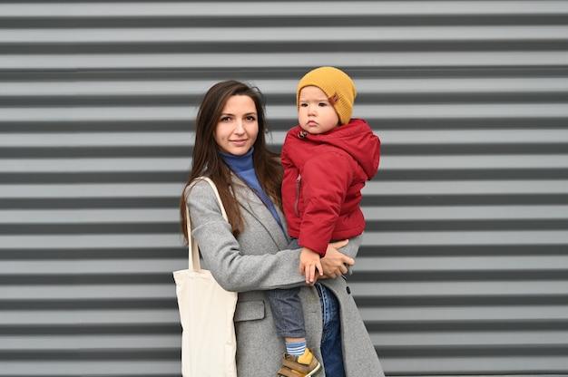 Retrato de mãe sorrindo com um bebê nos braços em roupas quentes em um fundo cinza