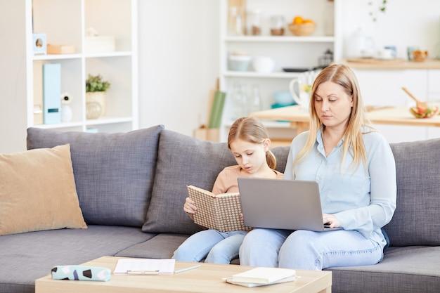 Retrato de mãe trabalhadora adulta usando laptop enquanto está sentado no sofá em casa com a filha lendo livro ao lado dela, copie o espaço