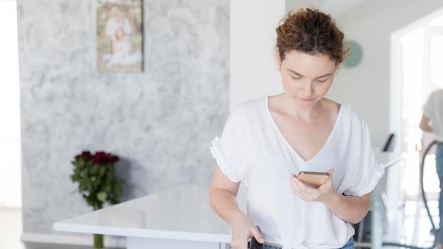 Retrato de mãe verificando seu telefone celular