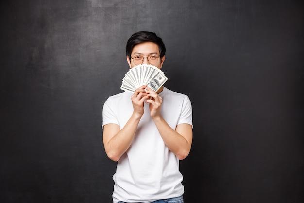 Retrato de manhoso feliz e satisfeito jovem asiático ganhando grande prêmio em dinheiro, escondendo o rosto atrás de leque de dólares, sorrindo com os olhos, decidir o que comprar nele, em pé