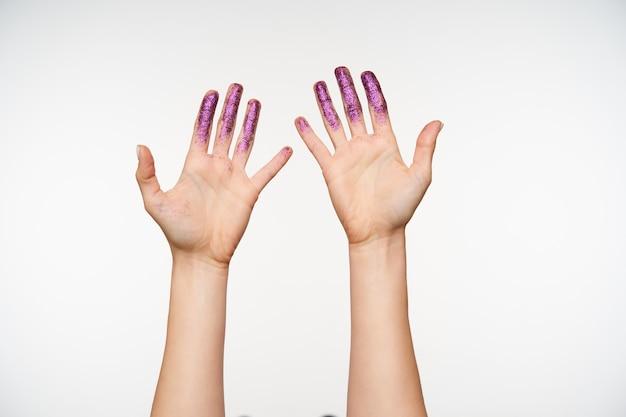 Retrato de mãos levantadas de mulher sendo levantadas enquanto mostra as palmas e mantendo todos os dedos brilhando separadamente, posando em branco