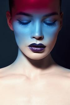 Retrato de maquiagem brilhante beleza contrastante de uma mulher em tons de sombra azul e vermelho