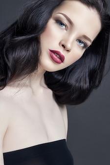 Retrato de maquiagem jovem morena. cuidado capilar