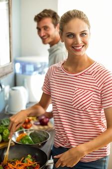 Retrato de marido e mulher a cozinhar comida em casa