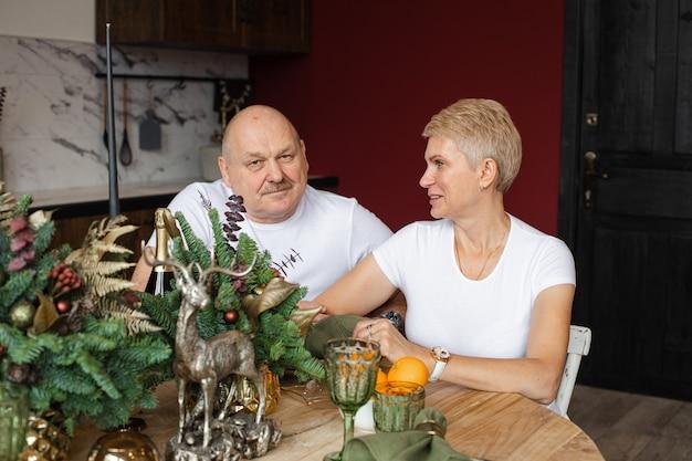 Retrato de marido e mulher em camisetas brancas, sentado à mesa decorada, comemorando o ano novo.