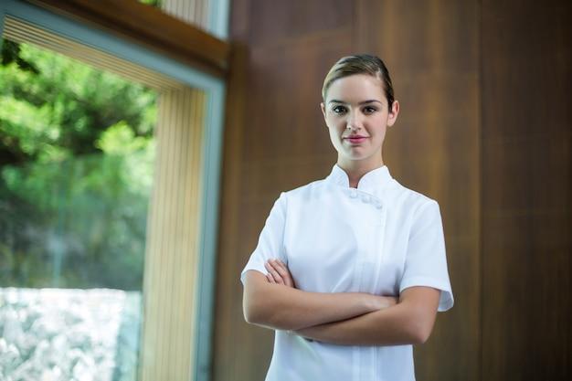 Retrato de massagista feminina confiante em pé com os braços cruzados
