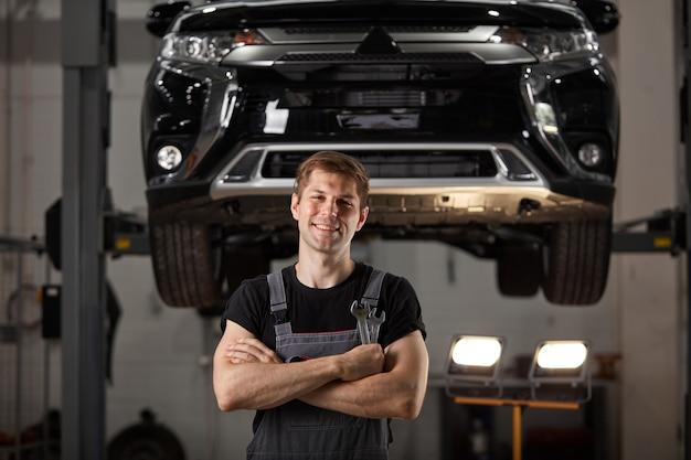 Retrato de mecânico confiante em uniforme posando em serviço de automóveis