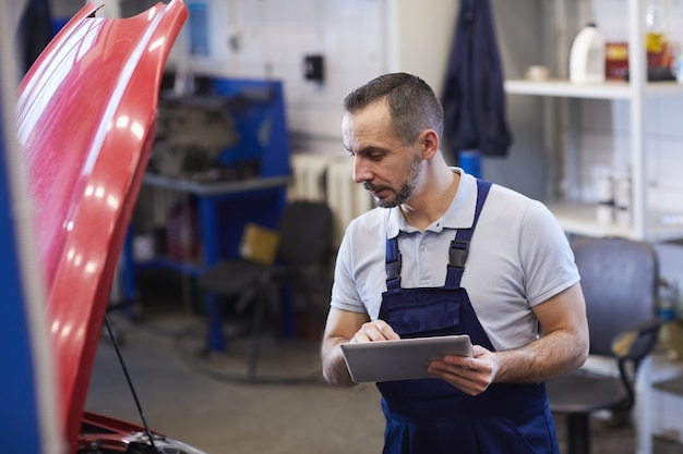 Retrato de mecânico de automóveis barbudo usando tablet digital durante a inspeção de veículos na oficina, copie o espaço da cintura para cima
