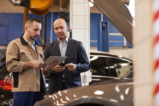 Retrato de mecânico de automóveis conversando com um empresário enquanto usa o tablet digital em uma oficina mecânica, copie o espaço