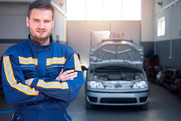 Retrato de mecânico de automóveis profissional em frente a oficina mecânica.