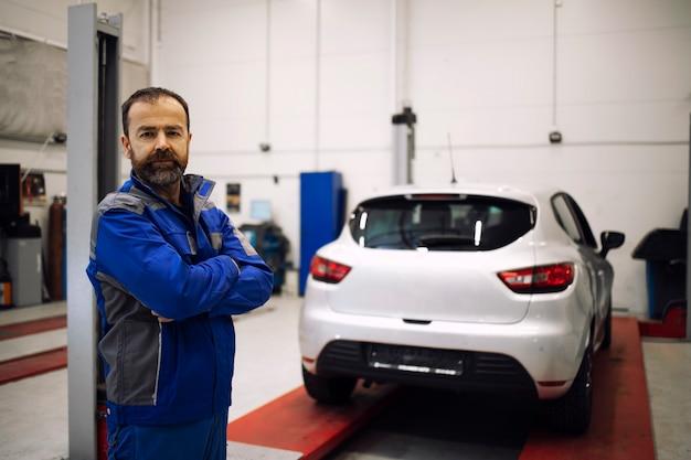 Retrato de mecânico de automóveis profissional em pé na oficina de veículos com os braços cruzados.