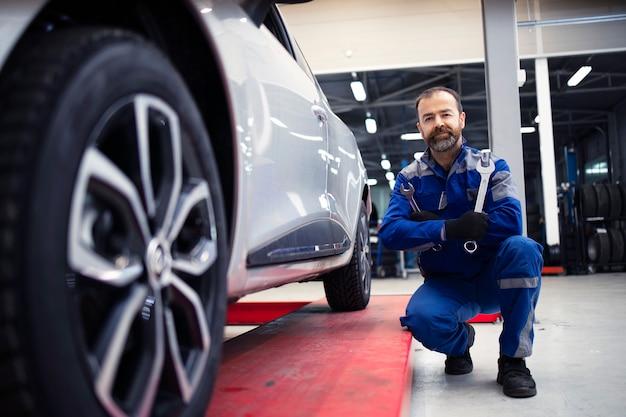Retrato de mecânico de automóveis profissional em pé na oficina de veículos por um automóvel e segurando ferramentas de chave inglesa.