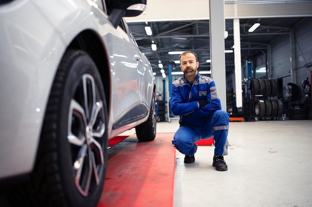 Retrato de mecânico de automóveis profissional em pé na oficina de veículos por um automóvel.