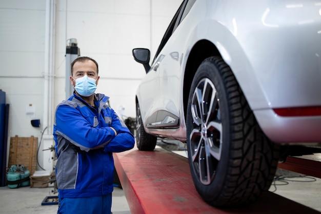 Retrato de mecânico de automóveis profissional usando máscara devido ao vírus corona parado na oficina de veículos por um automóvel.