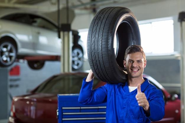Retrato de mecânico transportando um pneu