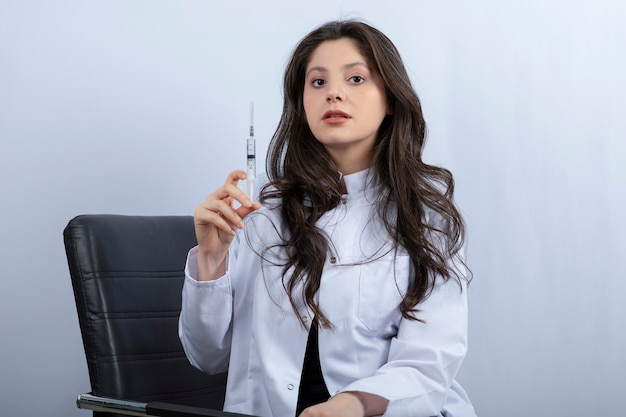 Retrato de médica em máscara médica e jaleco branco, segurando a seringa.