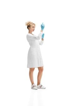 Retrato de médica, enfermeira ou cosmetologista em uniforme branco e luvas azuis em branco
