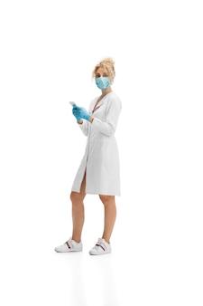 Retrato de médica enfermeira ou cosmetologista em uniforme branco e luvas azuis sobre branco