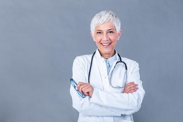 Retrato de médica sênior com estetoscópio & braço cruz isolado na parede